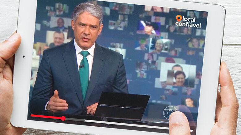 Pessoa segurando o tablet com o vídeo da reportagem, Willian Bonner na bancada do Jornal Nacional