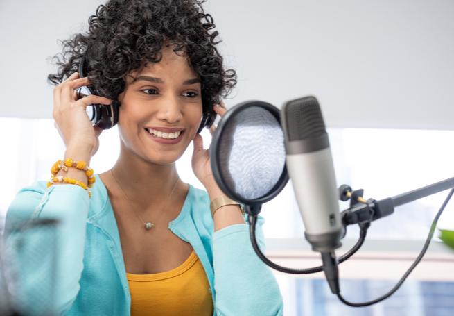 menina na frente de um microfone utilizando headfones